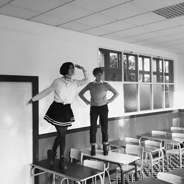 photo en noir et blanc de deux jeunes filles sur des bureaux dans une classe d'école vide